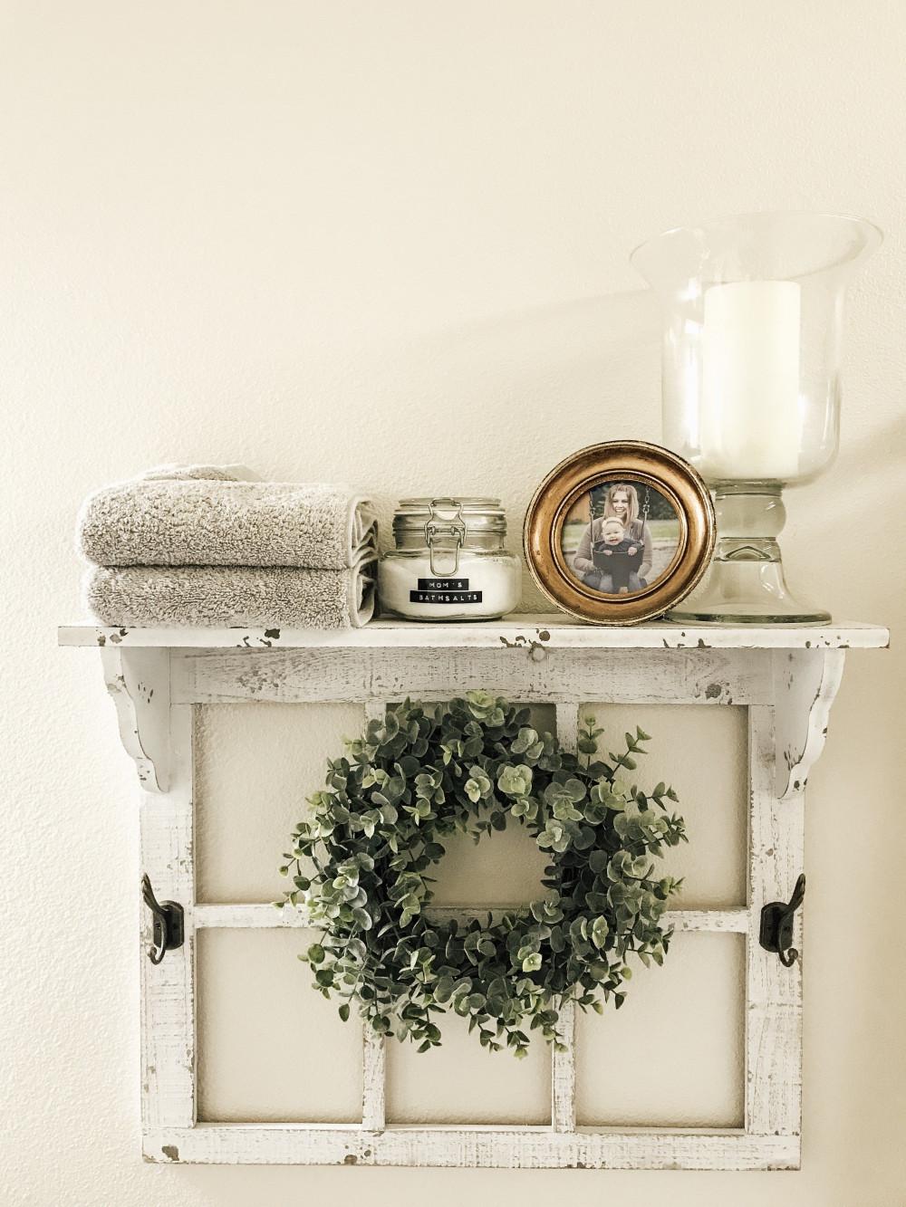 Hình 2. Một chiếc kệ đựng đồ dịu mát trong nhà tắm được kết hợp với khung cửa sổ cũ điểm vào giữa vòng nguyệt quế xanh tươi mang lại cảm giác sang trọng, thanh lịch.