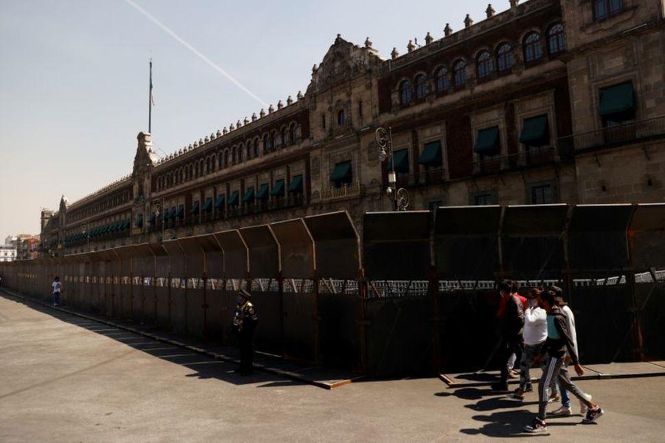 Mọi người đi qua hàng rào đặt bên ngoài Cung điện Quốc gia trước bạo lực dự kiến trong một cuộc biểu tình Ngày Phụ nữ, ở Thành phố Mexico