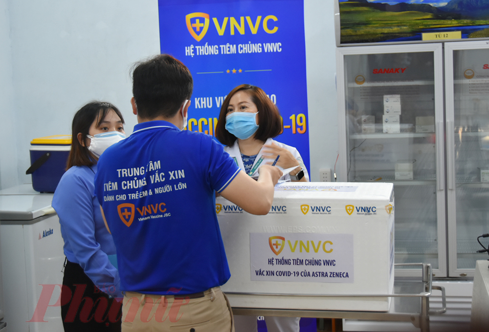 Nhân viên công ty VNVC bàn giao vắc-xin COVID-19 cho nhân viên y tế tại Bệnh viện Bệnh nhiệt đới, ảnh Phạm An