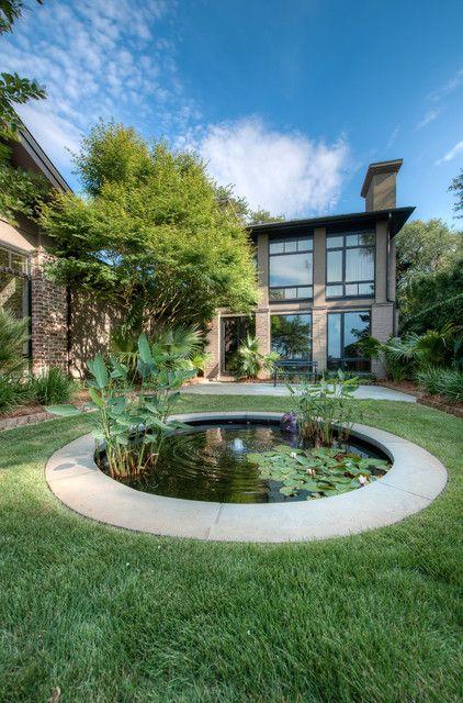 Hình 9. Một cái ao nhỏ hình tròn được xây trong lòng đất, với một đài phun nước ở trung tâm, cây xanh và hoa súng cùng những chú rùa, cá vùng vẫy tạo thành điểm nhấn thu hút cho ngôi nhà.