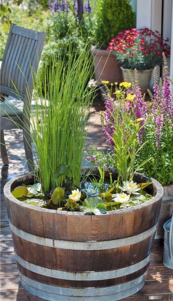 Thùng nước bằng gỗ đặt giữa sân với hoa súng và cây xanh làm nổi bật sự lãng mạn và mộc mạc cho không gian.