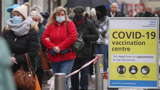 Người dân xếp hàng chờ tiêm vắc-xin COVID-19 tại Anh - Ảnh: AP