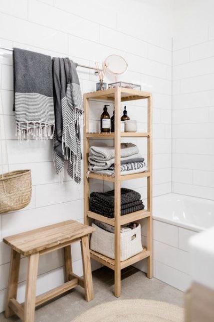 Hình 1. Kệ gỗ tối giản nhiều tầng để đựng khăn tắm đã được gấp lại gọn gàng, và nhiều đồ dùng cần thiết trong phòng tắm kết hợp với thanh móc treo những khăn đã sử dụng cho khô ráo là ý tưởng tích hợp tiện lợi.