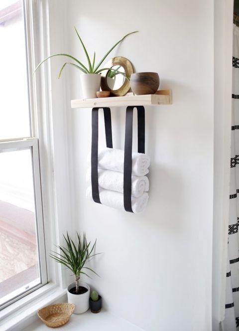 Kệ khăn bằng gỗ và dây da sẽ cho phép bạn lưu trữ không chỉ khăn tắm mà còn cả đồ trang trí và phụ kiện
