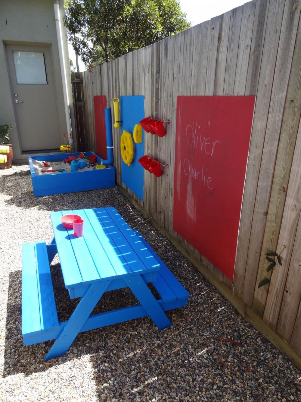 Khu vui chơi đầy màu sắc với hộp cát màu xanh lam tươi sáng, một số đồ trang trí bằng nhựa trên hàng rào và bộ bàn gỗ đáng yêu để bé vẽ tranh, tô tượng.