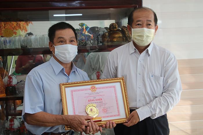 Phó Chủ tịch UBND tỉnh, phó Trưởng ban Thường trực Ban Chỉ đạo phòng chống dịch Covid-19 tỉnh Đồng Tháp Đoàn Tấn Bửu trao bằng khen cho ông Trần Xuân Định (bên trái)