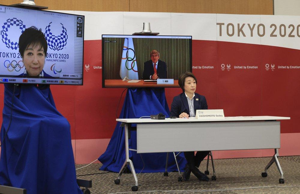 Chủ tịch Ủy ban Olympic Quốc tế (IOC) Thomas Bach (màn hình giữa) phát biểu tại cuộc họp trong khi Chủ tịch Ủy ban Tổ chức Olympic Tokyo 2020 Seiko Hashimoto (giữa) và Thống đốc Tokyo Yuriko Koike (màn hình trái) lắng nghe