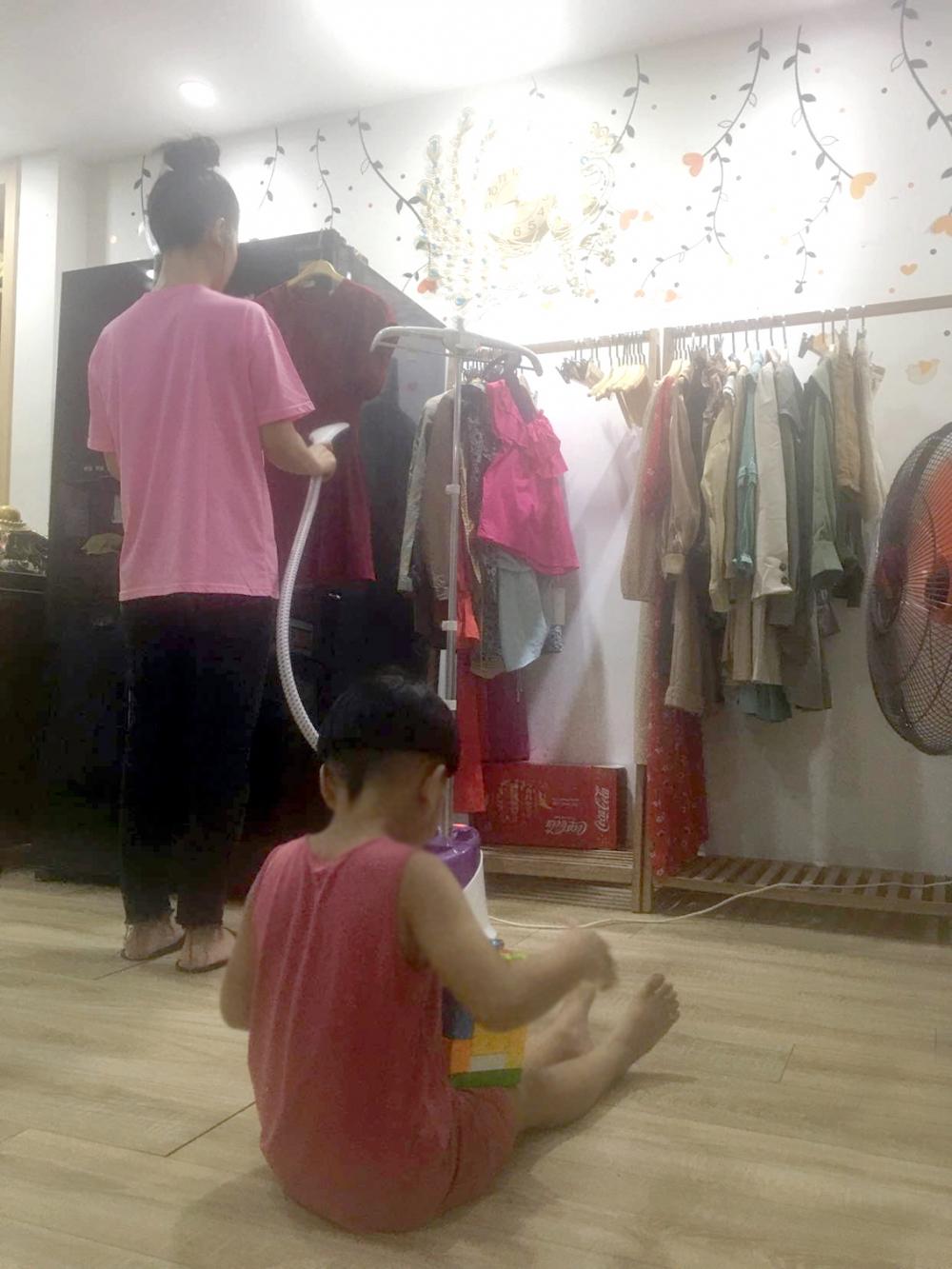 Vừa chơi với con, chị Kim M. vừa ủi quần áo để giao cho khách hàng