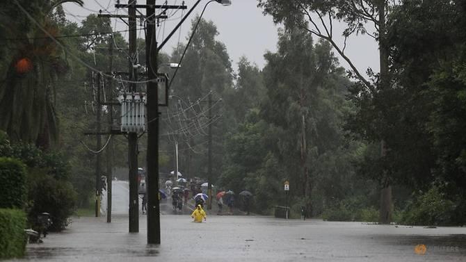 Một người lội qua dòng nước lũ gần sông Nepean đang dâng cao khi bang New South Wales trải qua lũ lụt trên diện rộng.