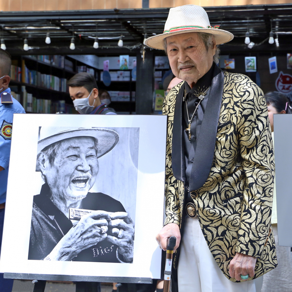Nghệ sĩ Tòng Sơn bên cạnh bức ảnh được nhiếp ảnh gia Thế Phong chụp