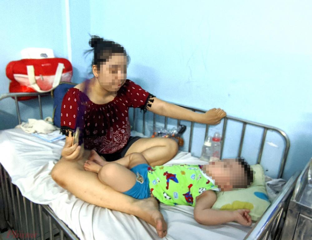 Chị Đ.T.T., quận Tân Bình đang chăm sóc con trai 20 tháng tuổi bị bệnh TCM. (Ảnh: Hiếu Nguyễn)
