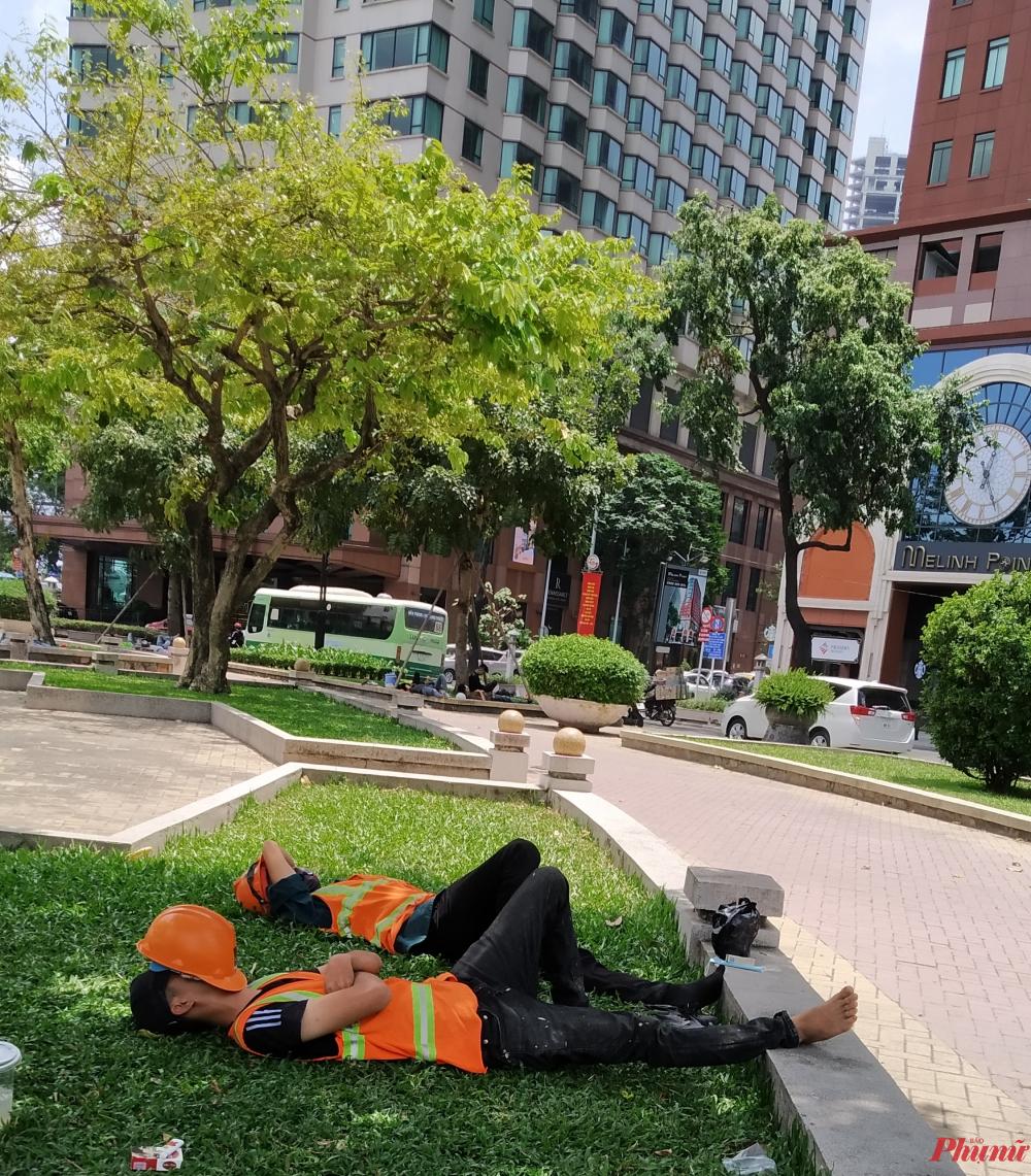 Dưới cái nắng oi bức, tại công viên trên đường Công trường Mê Linh (Q1), những người công nhân tranh thủ nghỉ ngơi lại sức cho buổi chiều làm việc.