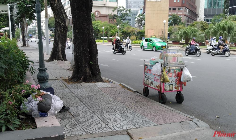 Người bán dạo đậu xe kem của mình ở ven đường Tôn Đức Thắng (Q1), ngả đầu lên chai nước suối dưới bóng mát để ngủ trưa. Anh đã bán hàng rong được 3 - 4 năm nay. Khi được hỏi thường nghỉ trưa chỗ nào, người đàn ông trả lời: 'Chỗ nào mát thì ghé vào nằm chỗ đó thôi.'