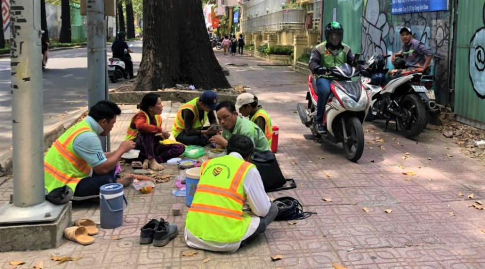 Sau những giờ làm việc vất vả, các công nhân làm cho một công trình ở góc đường Pasteur - Nguyễn Đình Chiểu tập trung trên vỉa hỉa ăn bữa cơm vội