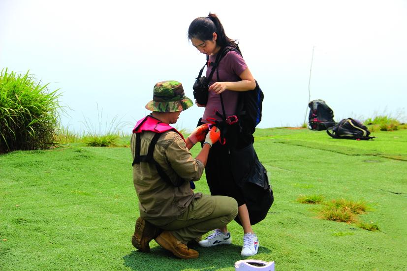 Kiểm tra kỹ lưỡng và đảm bảo an toàn cho người chơi. Trong ảnh là phi công đang lắp dây bảo hộ cho Sương, một bạn nữ từ Hà Nội vào Đà Nẵng du lịch và tham gia bay dù lượn