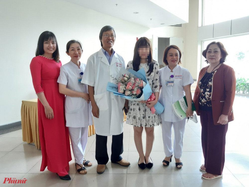 Bệnh nhân Ngô Hoàng N. chụp hình cùng các bác sĩ, người thân trước lúc ra viện