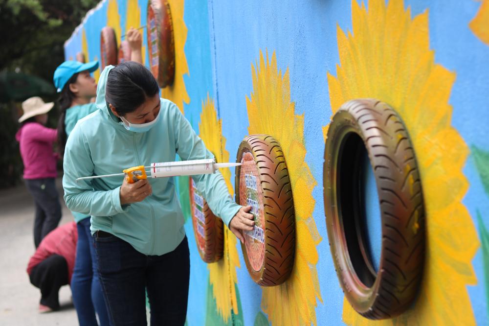 Mọi người cùng vẽ hoa và tận dụng lốp xe làm thành phần nhụy rồi gắn các thông điệp kêu gọi chung tay bảo vệ môi trường, bảo vệ trẻ em.