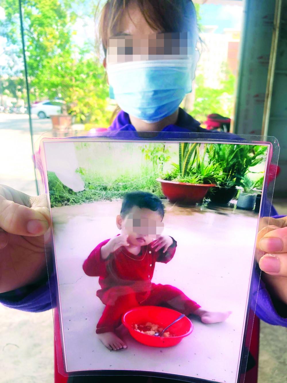 Chị N.M.N. cầm bức ảnh của con đến phiên tòa giành quyền nuôi con