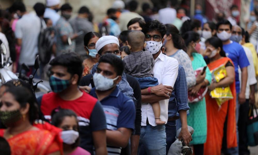 Người dân xếp hàng mua sắm tại một khu chợ đông đúc giữa ở Mumbai giữa lúc dịch bệnh hoành hành