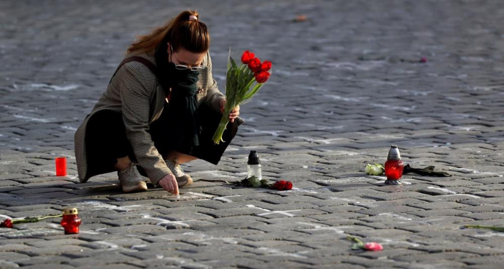 Người phụ nữ tại Cộng hòa Séc ghi tên người thân đã qua đời vì COVID-19 lên mặt đất, tại quảng trường ở thủ đô Prague nhân kỷ niệm 1 năm ngày đảo quốc ghi nhận ca tử vong đầu tiên vì COVID-19 hôm 26/3/2021