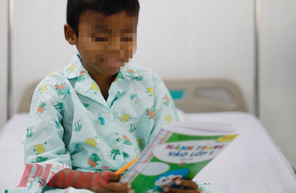 Bé M. say mê ngắm nghía quyển sách, với quả thận của cha, bé sẽ sớm được về nhà đi học