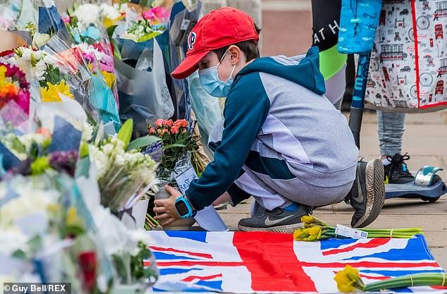 Một cậu bé cầm chậu hoa đặt bên ngoài Cung điện Buckingham sau khi Hoàng tử Philip qua đời.