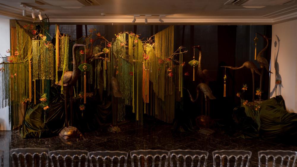 Ở tầng thứ ba của triển lãm là một không gian đậm chất đông dương. Bảo Nam kết hợp hoa, nghệ thuật cắm hoa cùng bàn, tủ gỗ, những tượng điêu khắc gỗ, bình gốm sứ quý giá. Tác phẩm với những chú hạc to lớn ngậm hoa này do 30 người thực hiện.