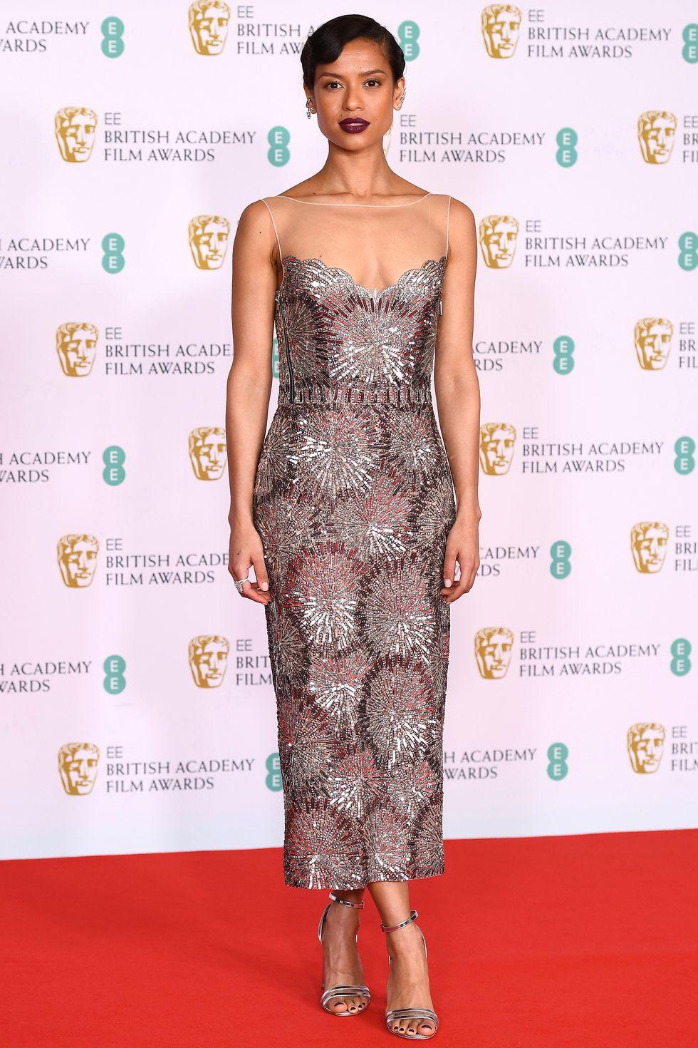 Gugu Mbatha-Raw luôn biết cách ghi điểm nhờ phong cách thời trang và lối trang điểm sang trọng. Cô nàng chọn chiếc váy Louis Vuitton ánh kim và trang sức Messika trên thảm đỏ BAFTA.
