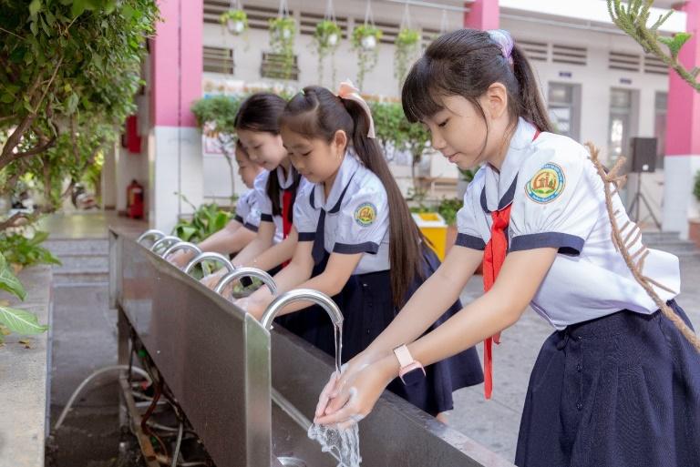 Các em học sinh trải nghiệm bồn rửa tay thông minh. Ảnh: AEON Việt Nam