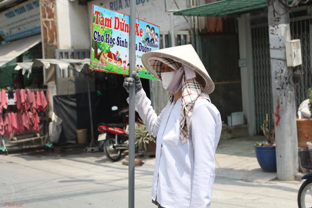 Ngày 2 buổi trưa - chiều, bà Hai Trị ra giữa đường cầm bảng Tạm dừng xe cho học sinh qua đường