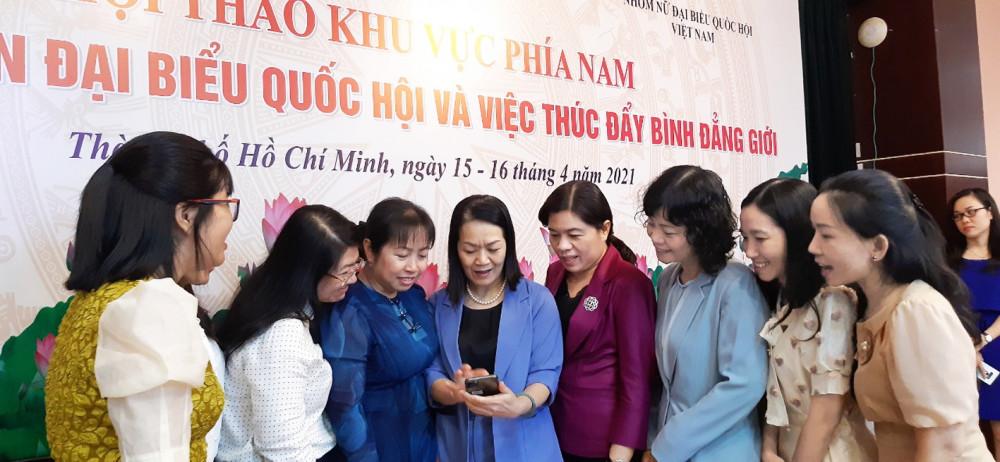 Bà Bùi Thị Hòa - Phó chủ tịch Hội LHPN Việt Nam (thứ năm từ phải qua) giới thiệu với các nữ đại biểu về sản phẩm truyền thông của Hội liên quan tuyên truyền bầu cử ảnh: nghi anh