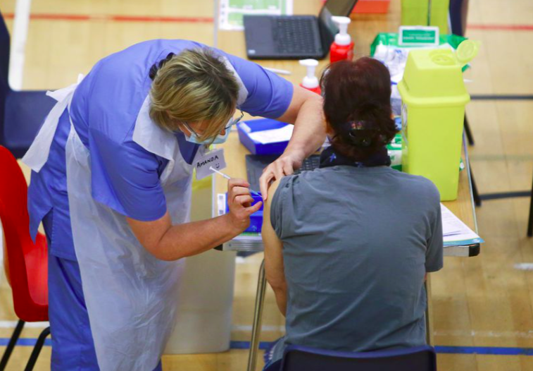 Một phụ nữ được tiêm vắc-xin Oxford-AstraZeneca tại trung tâm tiêm chủng COVID-19 ở Sân vận động Cwmbran ở Cwmbran, South Wales, Anh ngày 17/2/2021- Ảnh: Reuters