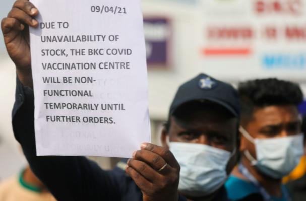 Một người bảo vệ giơ thông báo để thông báo cho mọi người về tình trạng thiếu nguồn cung cấp vắc xin phòng bệnh do coronavirus (COVID-19) tại một trung tâm tiêm chủng, ở Mumbai, Ấn Độ, ngày 9 tháng 4 năm 2021. REUTERS / Francis Mascarenhas / File Photo