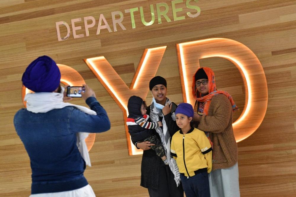 Một gia đình chụp ảnh trước chuyến bay đến New Zealand tại Sân bay Quốc tế Sydney