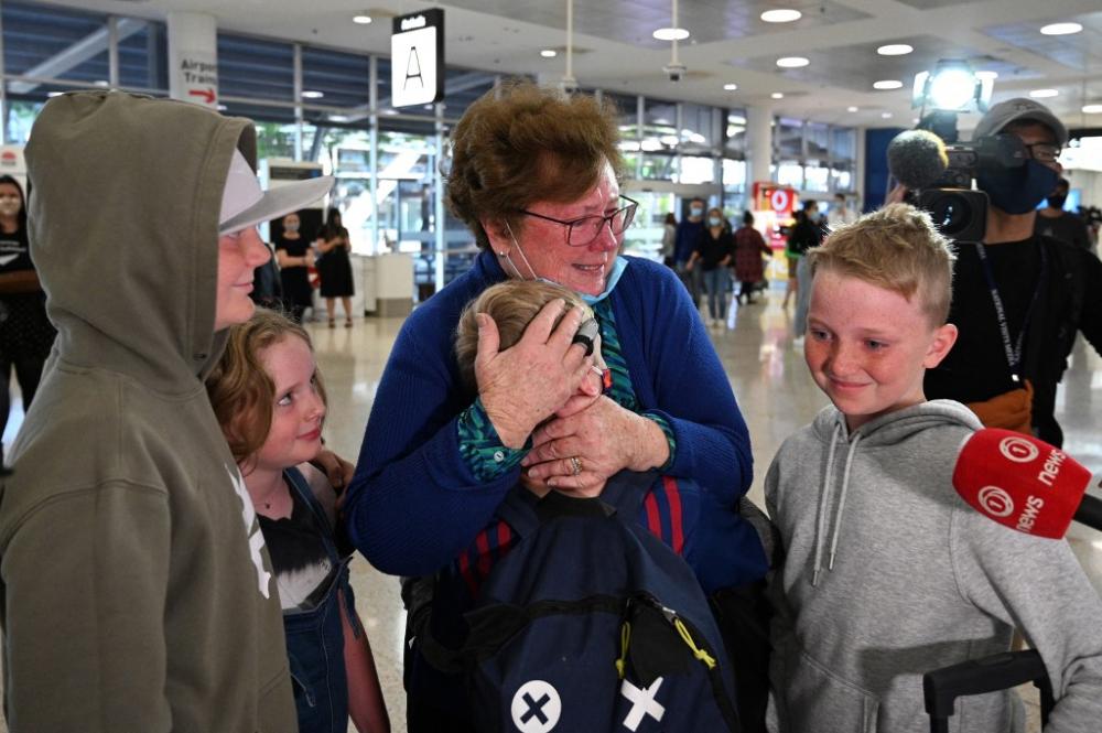 Một người phụ nữ ôm các thành viên trong gia đình khi họ từ New Zealand đến sân bay quốc tế Sydney