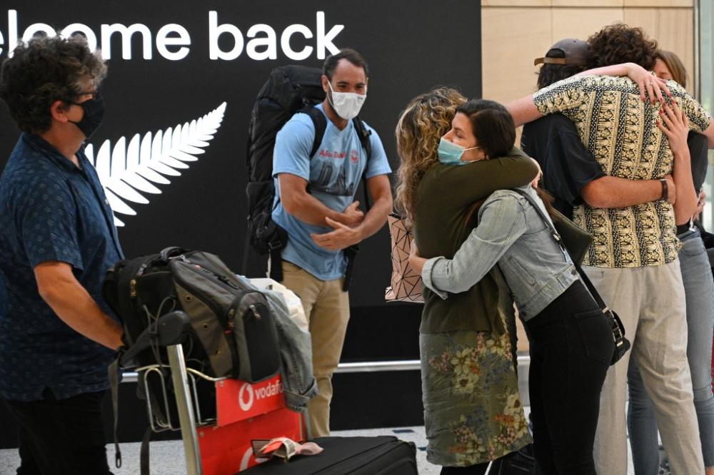 Các thành viên trong gia đình ôm nhau khi họ từ New Zealand đến sân bay quốc tế Sydney