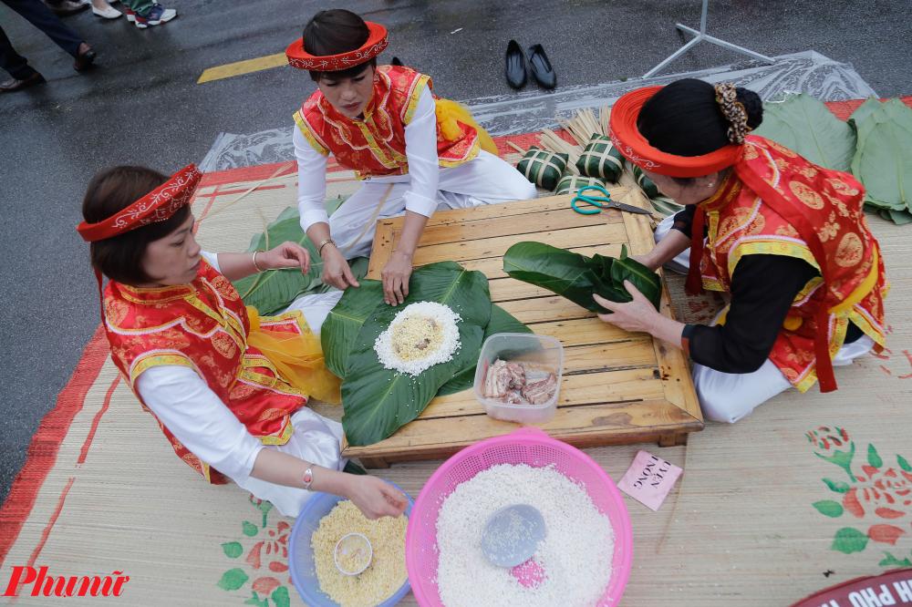 Nghệ nhân của các huyện trong tỉnh Phú Thọ đang biểu diễn gói bánh chưng.