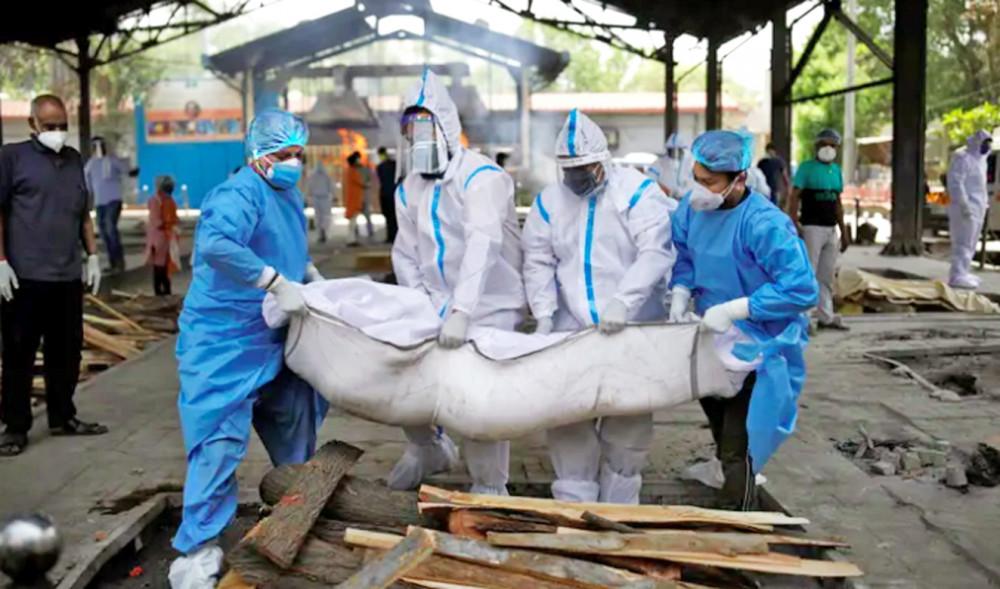 Nhân viên y tế và người thân khiêng thi thể chết vì COVID-19 tại một lò hỏa táng ở New Delhi - Ảnh: Reuters