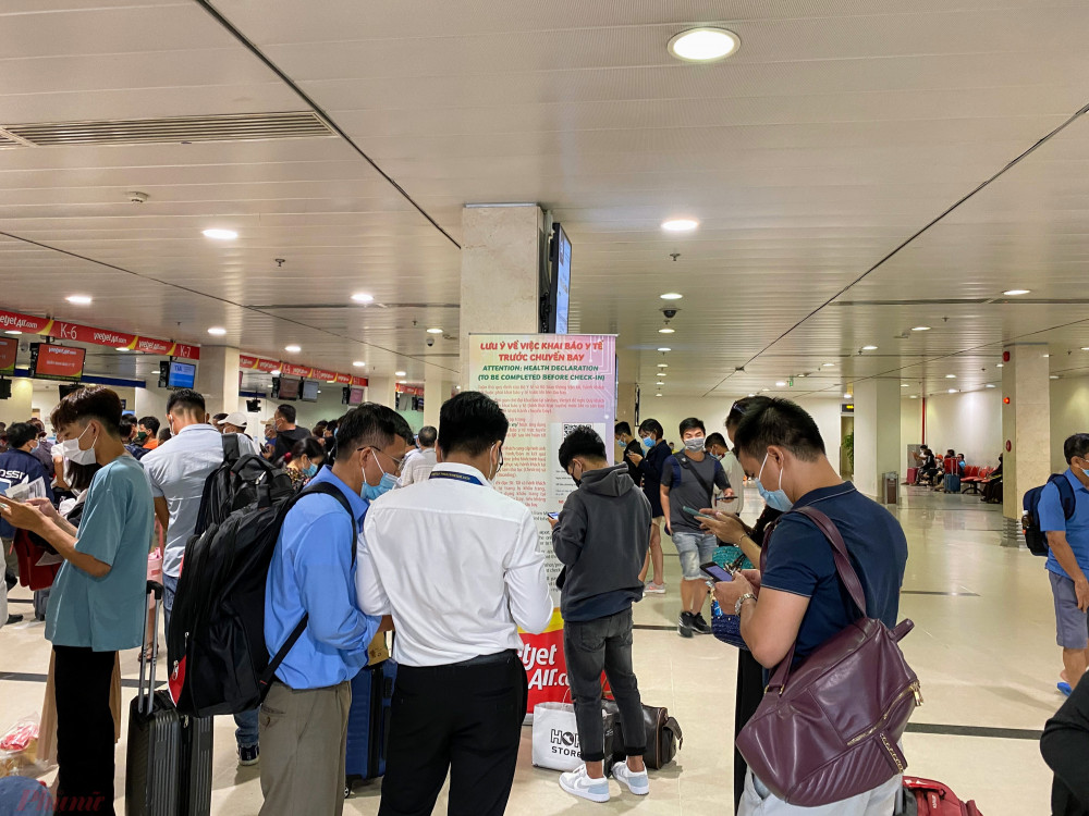 Hành khách gần đến giờ bay mới bắt đầu tiến hành khai báo y tế tại Cảng hàng không quốc tế Tân Sơn Nhất. Ảnh: Quốc Thái