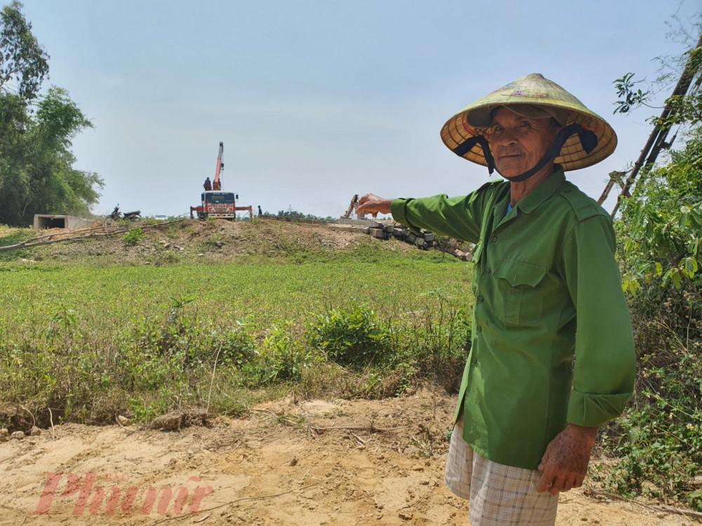 Ông Nguyễn Hoàng Sinh trên mảnh đất của mình, phía trước là tuyến đường ven sông đang đứng bánh do công tác đền bù chưa thỏa đáng