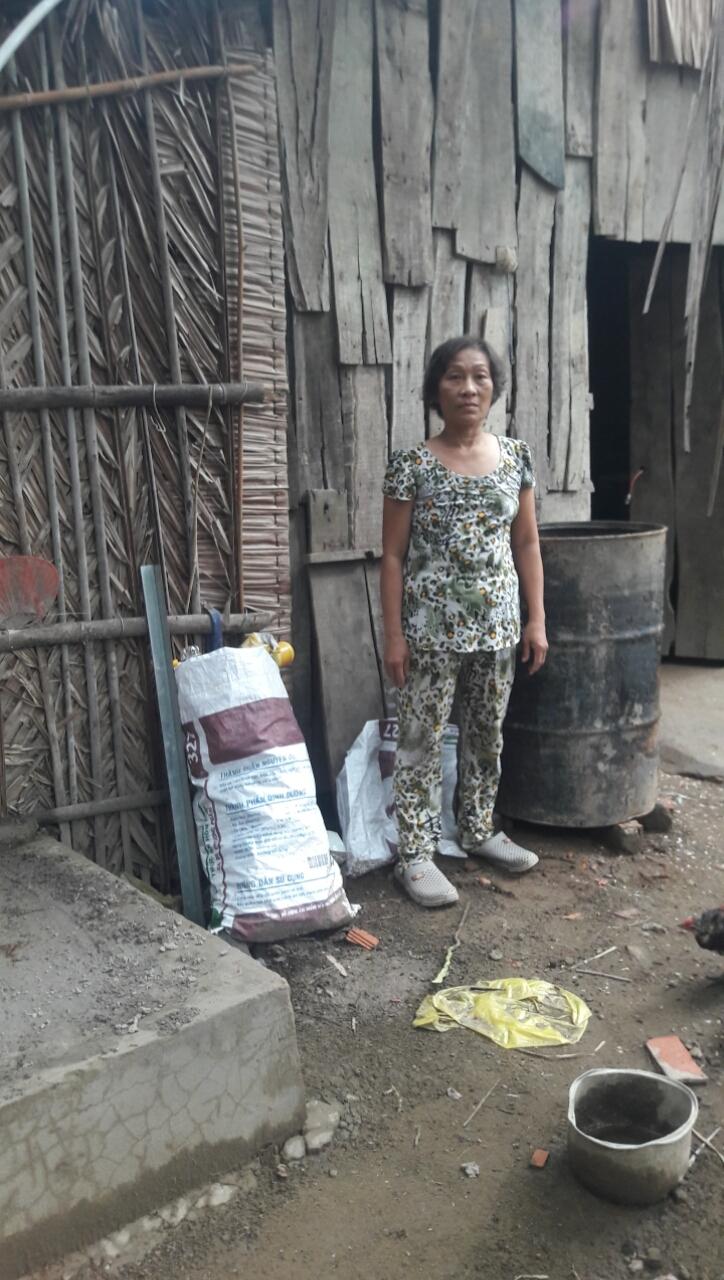Chị Nguyễn Thị Nhiều bên ngôi nhà vách lá của mình