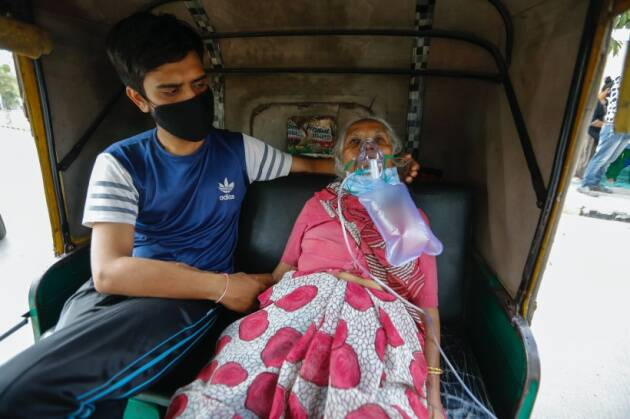 Một bệnh nhân COVID-19 đeo mặt nạ dưỡng khí chờ được nhập viện ở Ahmedabad