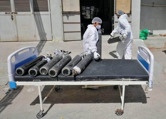 Công nhân sử dụng giường để vận chuyển các bình oxy rỗng đến trạm nạp tại bệnh viện COVID-19 ở Ahmedabad