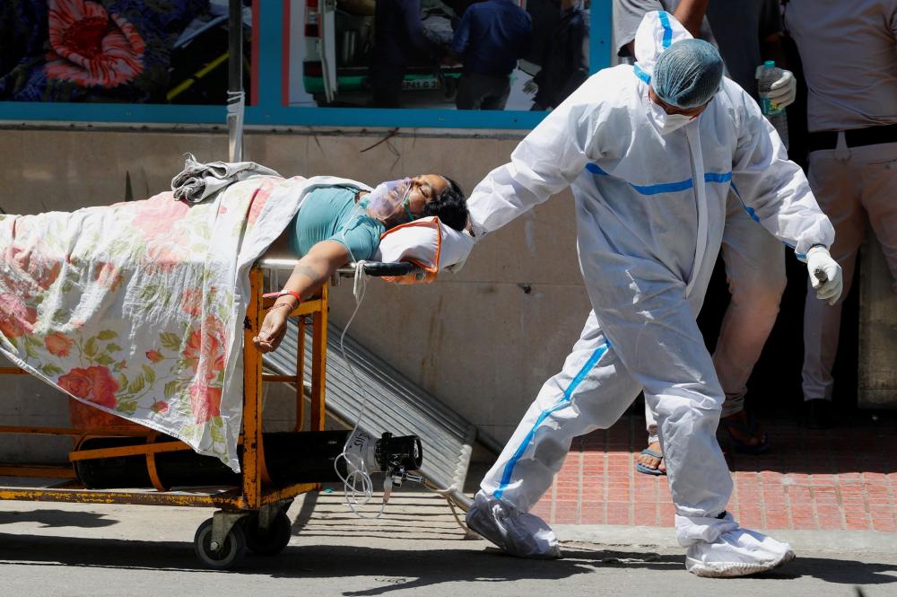 Một nhân viên y tế mặc thiết bị bảo vệ cá nhân (PPE) di chuyển một bệnh nhân COVID-19 bên ngoài khu cấp cứu Bệnh viện Guru Teg Bahadur, New Delhi, Ấn Độ - Ảnh: Reuters