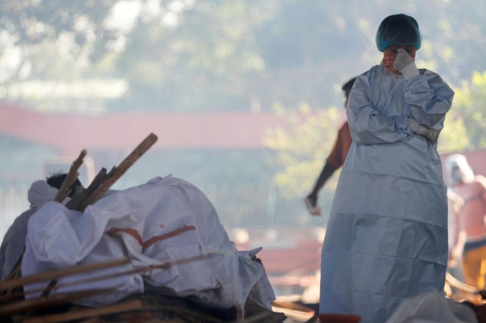 Một cậu bé đứng bên cạnh thi thể của người cha đã chết vì COVID-19 tại một điểm hỏa táng ở New Delhi, Ấn Độ ngày 24/4 - Ảnh: Reuters
