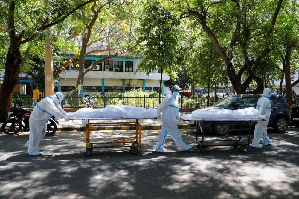 Các nhân viên y tế mang thiết bị bảo vệ cá nhân (PPE) chuyển thi thể các nạn nhân COVID-19 tại Bệnh viện Guru Teg Bahadur, New Delhi, Ấn Độ, ngày 24/4 - Ảnh: Reuters