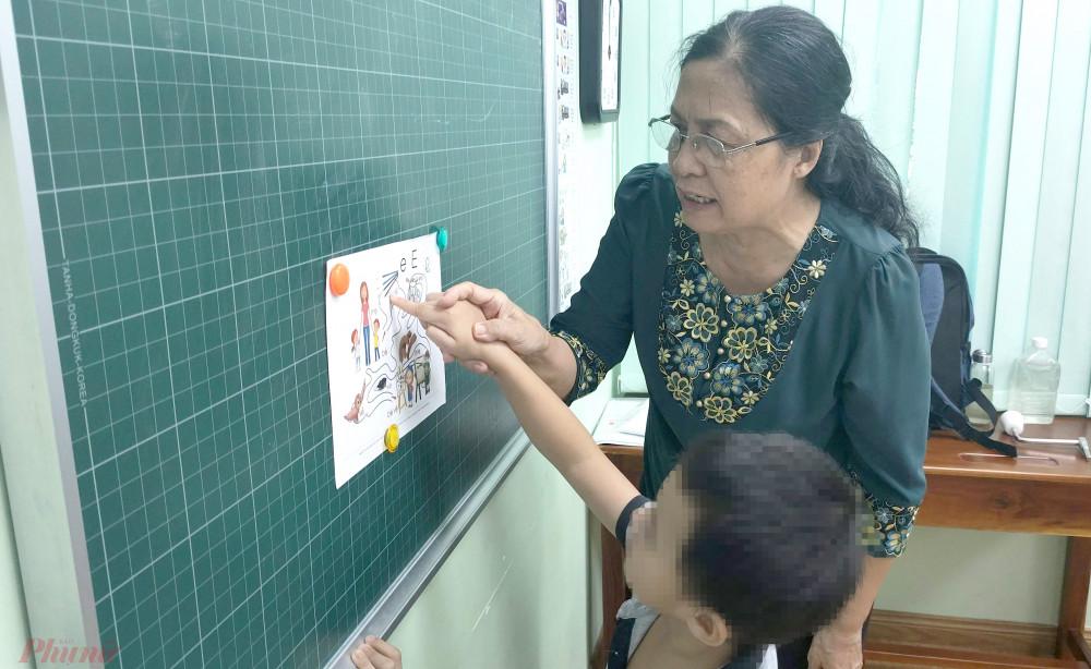 Phó giáo sư Nguyễn Thị Ly Kha đang hướng dẫn bé K.L. học vần qua bài tập tìm đường đi