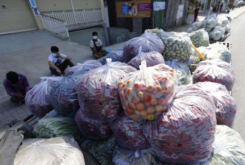 Tiểu thương bán rau trên một đường phố Phnom Penh bị phong tỏa - Ảnh: EPA-EFE