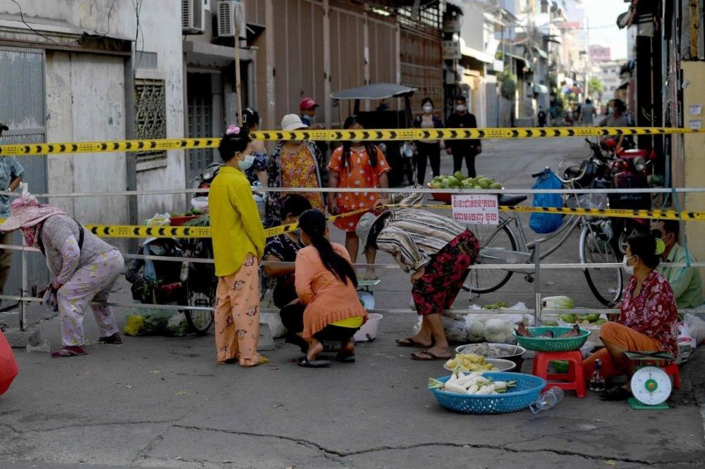 Người dân mua rau bên cạnh một rào chắn được thiết lập trong khu phố theo quy định phong tỏa nhằm ngăn chặn sự tăng vọt của các ca nhiễm COVID-19 ở thủ đô Phnom Penh - Ảnh: AFP