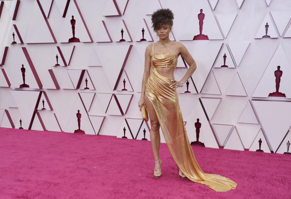 Andra Day gợi cảm trong trang phục vàng đồng được làm hoàn toàn từ kim loại của Vera Wang. Cô nàng không quên sử dụng ví cầm tay và giày cao gót đồng màu để tạo sự hài hòa cho set đồ.